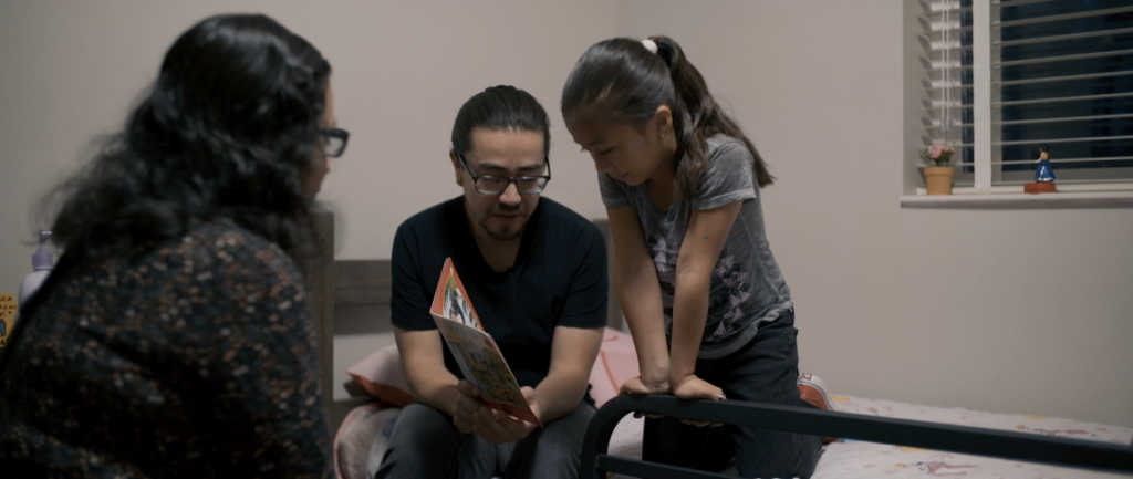 Osvaldo Sandoval, a DACA recipient, reads a book to his daughter with his wife Juana Montoya.
